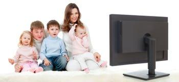 Lycklig familj som sitter på golv och den hållande ögonen på TV:N arkivbilder