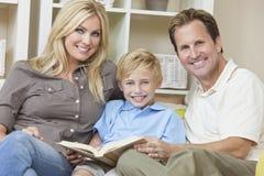 Lycklig familj som sitter på sofaen som läser en bok Arkivbild