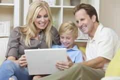 Lycklig familj som sitter på sofaen genom att använda bärbar datordatoren Arkivfoto