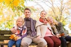Lycklig familj som sitter utomhus på bänk i höst Royaltyfri Bild