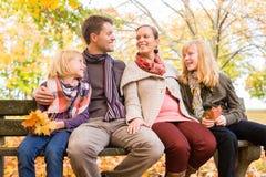 Lycklig familj som sitter utomhus på bänk i höst fotografering för bildbyråer