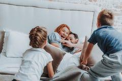 Lycklig familj som slåss vid kudden i säng royaltyfri bild
