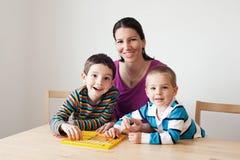 Lycklig familj som spelar en brädelek royaltyfri bild