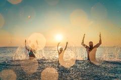 Lycklig familj som spelar i havet royaltyfria bilder