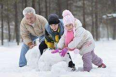 Lycklig familj som spelar i ny snö royaltyfri fotografi