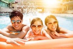 Lycklig familj som spelar i simbassäng royaltyfri bild