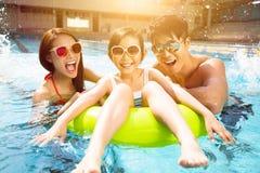 Lycklig familj som spelar i simbassäng Royaltyfria Bilder