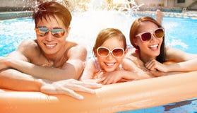 Lycklig familj som spelar i simbassäng royaltyfria foton