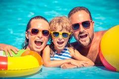 Lycklig familj som spelar i simbassäng Royaltyfri Fotografi