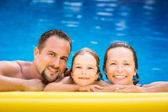 Lycklig familj som spelar i simbassäng Arkivfoton