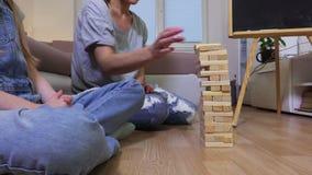 Lycklig familj som spelar leken med träkvarter hemma arkivfilmer