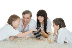Lycklig familj som spelar lottot Arkivbild