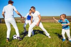 Lycklig familj som spelar med en boll på naturen i våren, sommar royaltyfri fotografi