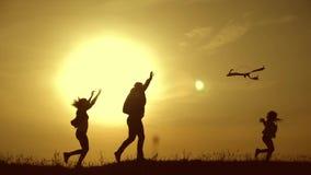Lycklig familj som spelar med en drake medan p? ?ngen, solnedg?ng, i sommardag Rolig familjtid Lycklig liten flickalansering a arkivfilmer