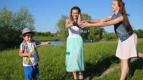 Lycklig familj som spelar med såpbubblor på naturen nära sjön i sommar stock video