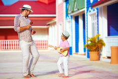 Lycklig familj som spelar musik och dansar på den karibiska gatan arkivbild