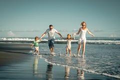 Lycklig familj som spelar på stranden på dagtiden Royaltyfri Foto