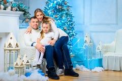 Lycklig familj som står den near julgranen fotografering för bildbyråer