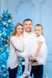 Lycklig familj som står den near julgranen royaltyfri fotografi