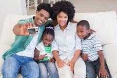 Lycklig familj som tar en selfie på soffan royaltyfri foto