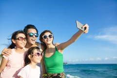 Lycklig familj som tar en selfie på stranden royaltyfri fotografi