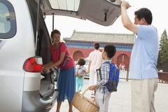 Lycklig familj som tar material ut från bilen som förbereder sig för picknick Royaltyfri Fotografi