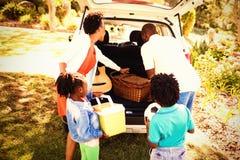 Lycklig familj som tar objekt ut ur bilen arkivbild