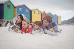 Lycklig familj som tar selfie, medan ligga på sand Royaltyfri Bild