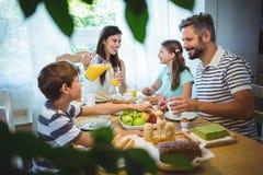 Lycklig familj som till varandra talar, medan ha frukosten tillsammans royaltyfria bilder