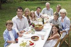 Lycklig familj som tillsammans äter middag i trädgård Royaltyfri Fotografi