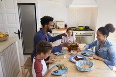 Lycklig familj som tillsammans äter på deras köksbord royaltyfria bilder
