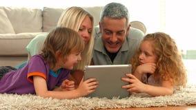 Lycklig familj som tillsammans använder minnestavlan stock video