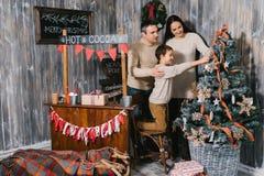Lycklig familj som tillsammans dekorerar julgranen royaltyfri foto