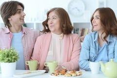 Lycklig familj som tillsammans dricker te Fotografering för Bildbyråer