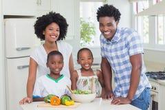 Lycklig familj som tillsammans förbereder grönsaker arkivfoton