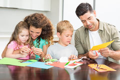 Lycklig familj som tillsammans gör konsthantverk på tabellen Royaltyfri Foto