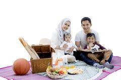 Lycklig familj som tillsammans har picknick på studio Royaltyfri Fotografi