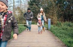 Lycklig familj som tillsammans kör i skogen royaltyfri foto