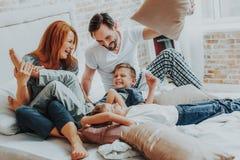 Lycklig familj som tillsammans kopplar av i säng i morgon royaltyfria bilder