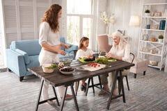 Lycklig familj som tillsammans lagar mat den sunda matställen Arkivfoto