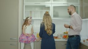 Lycklig familj som tillsammans lagar mat i köket lager videofilmer