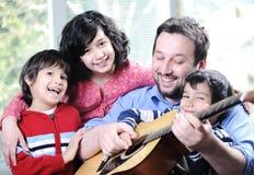 Lycklig familj som tillsammans spelar gitarren Royaltyfri Bild