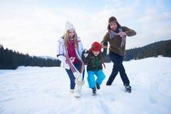 Lycklig familj som tillsammans spelar i snö på vintern royaltyfri foto