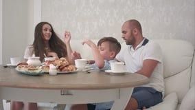 Lycklig familj som tillsammans spelar, medan ha frukosten på restaurangtabellen arkivfilmer