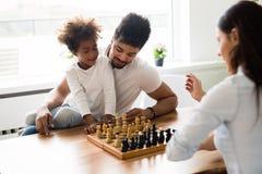 Lycklig familj som tillsammans spelar schack hemma Royaltyfri Bild