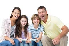 Lycklig familj som tillsammans spelar videospelet Fotografering för Bildbyråer