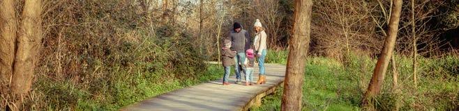 Lycklig familj som tillsammans talar och spelar i skogen royaltyfria foton