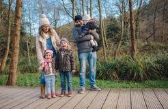 Lycklig familj som tillsammans tycker om fritid i skogen royaltyfri foto