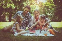 Lycklig familj som tillsammans tycker om i picknick Familj i äng Arkivfoton