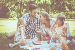 Lycklig familj som tillsammans tycker om i picknick Familj i äng Royaltyfri Fotografi